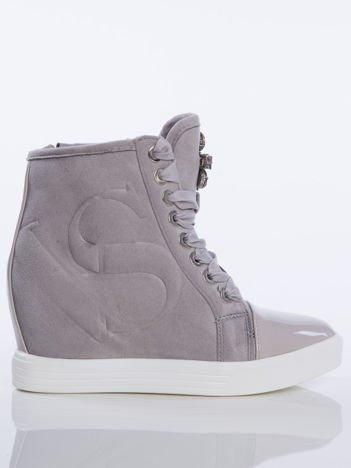 Szare zamszowe sneakersy z tłoczoną literką na boku cholewki, sznurowane ozdobną tasiemką z błyszczącymi kamieniami na przodzie