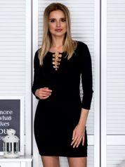 Czarna sukienka z ozdobnymi kółeczkami przy dekolcie