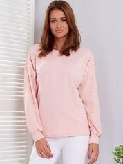 Jasnoróżowa bluzka ozdobiona perełkami