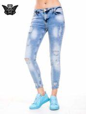 Niebieskie spodnie jeansowe z dziurami i rozdarciami