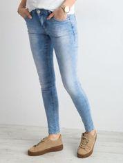 Niebieskie spodnie rurki jeansowe