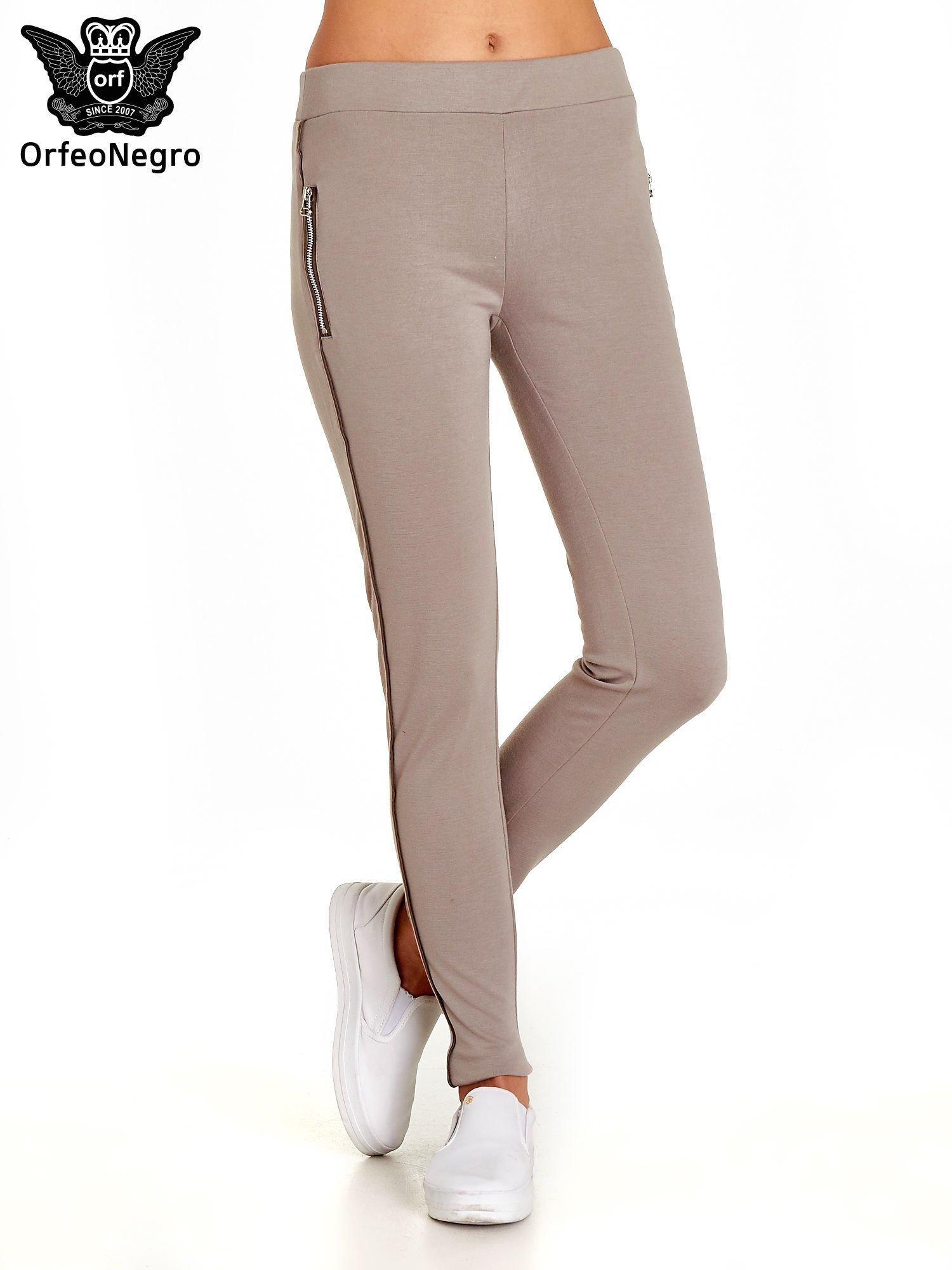 269e7f03223d09 Beżowe spodnie materiałowe tregginsy ze skórzanym lampasem i zamkami ...