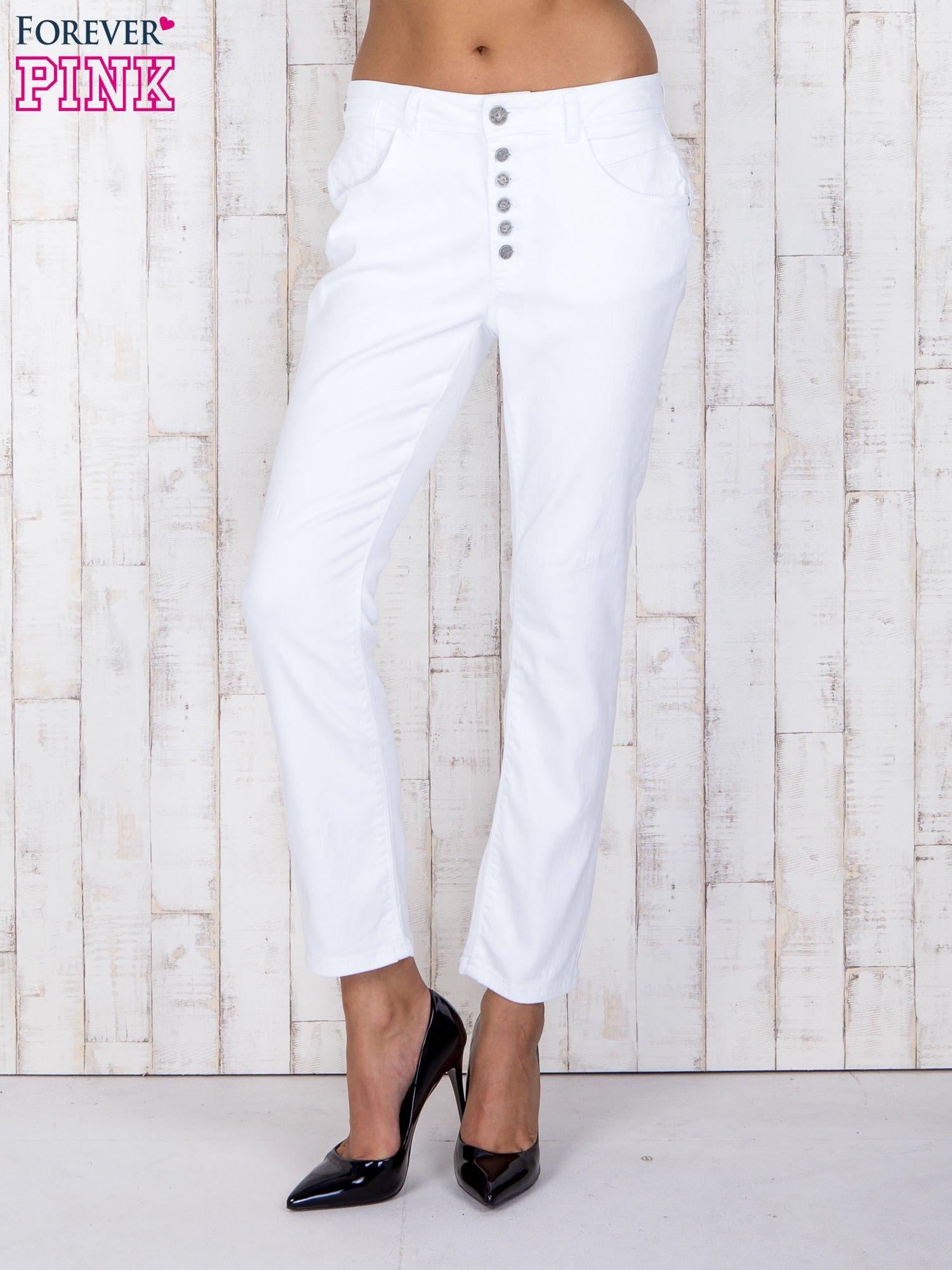 Białe jeansowe spodnie z przetarciami i guzikami                                  zdj.                                  1