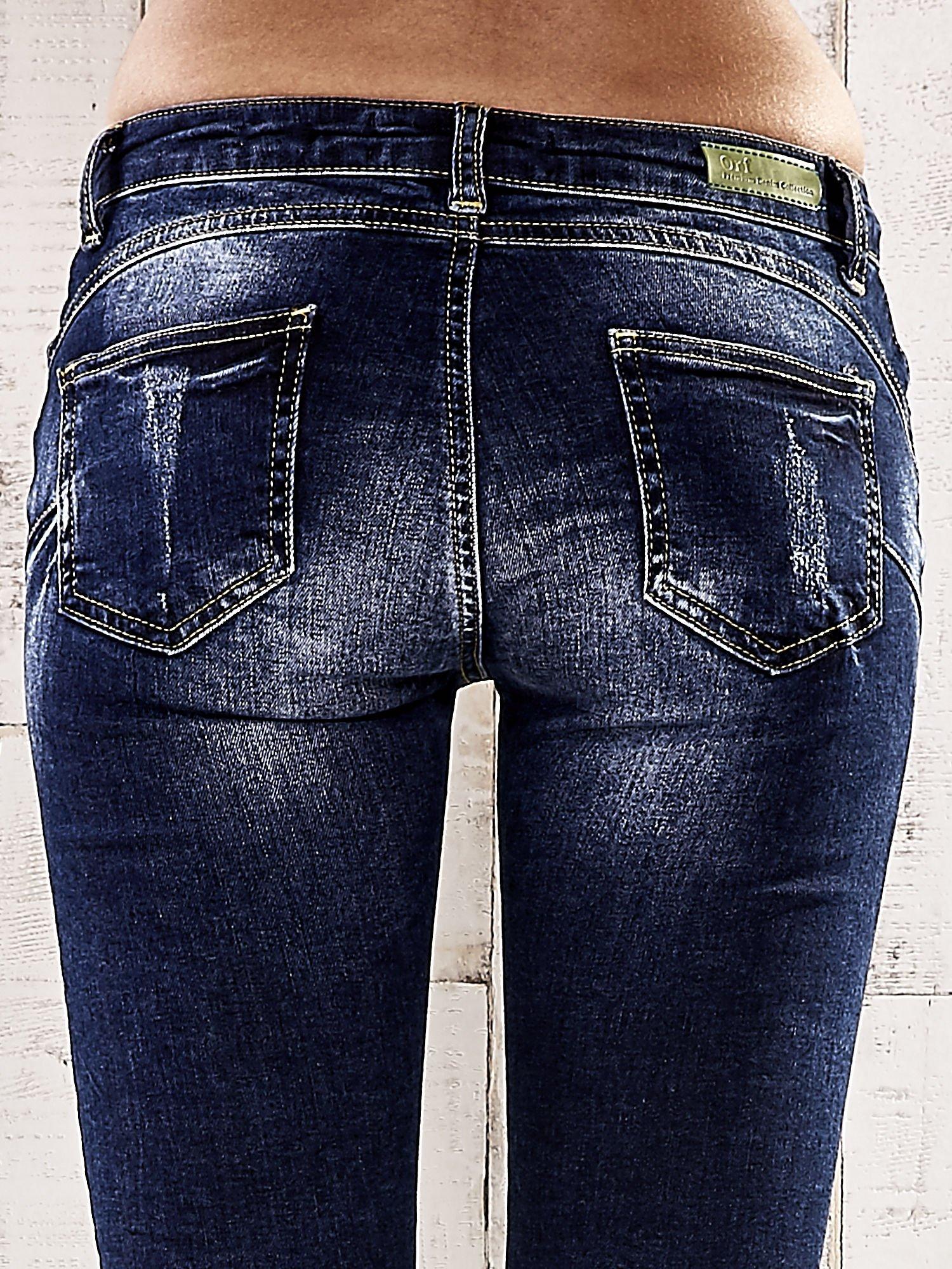 Ciemnoniebieskie spodnie rurki z dekatyzowaniem i przetarciami                                  zdj.                                  6