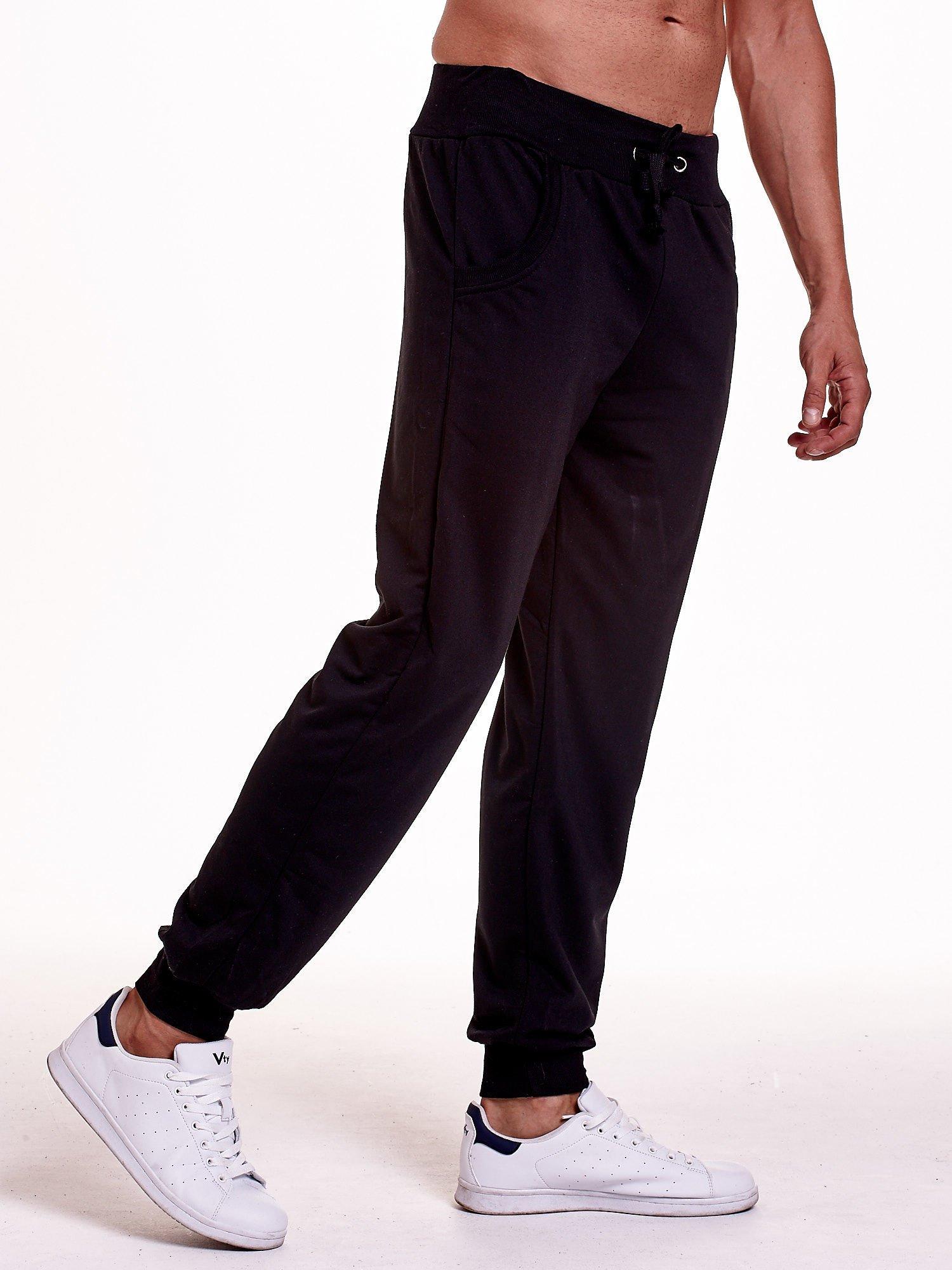 Czarne dresowe spodnie męskie z trokami w pasie i kieszeniami                                  zdj.                                  3
