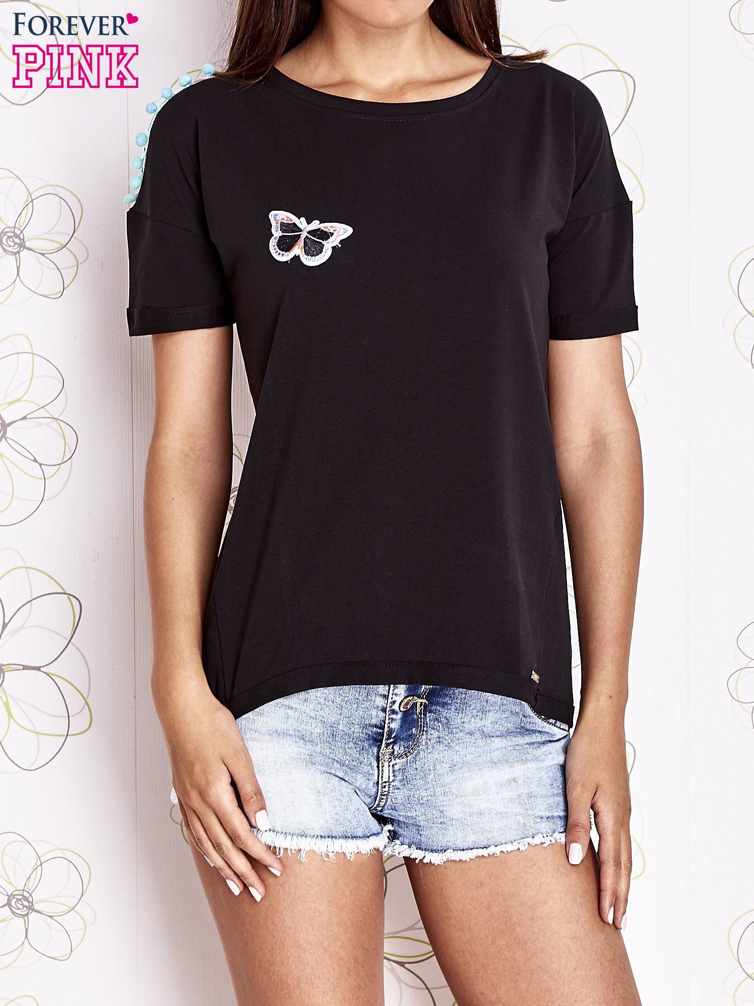 Czarny t-shirt z naszywką motyla i pomponami                                  zdj.                                  1
