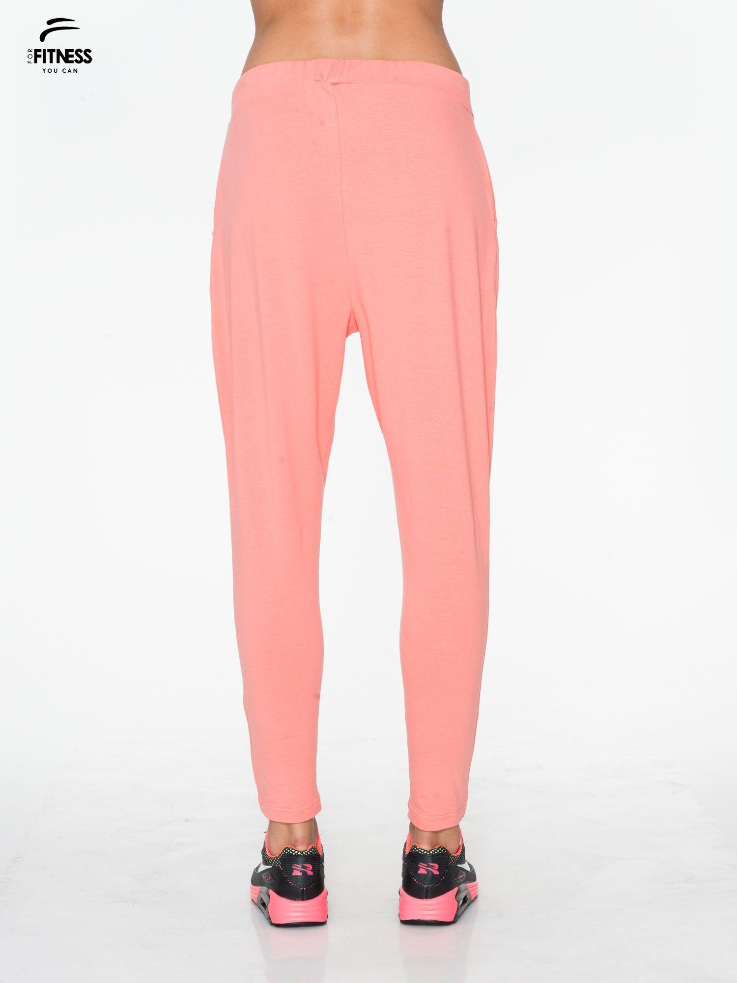 Jasnokoralowe spodnie dresowe typu baggy z guziczkami                                  zdj.                                  3