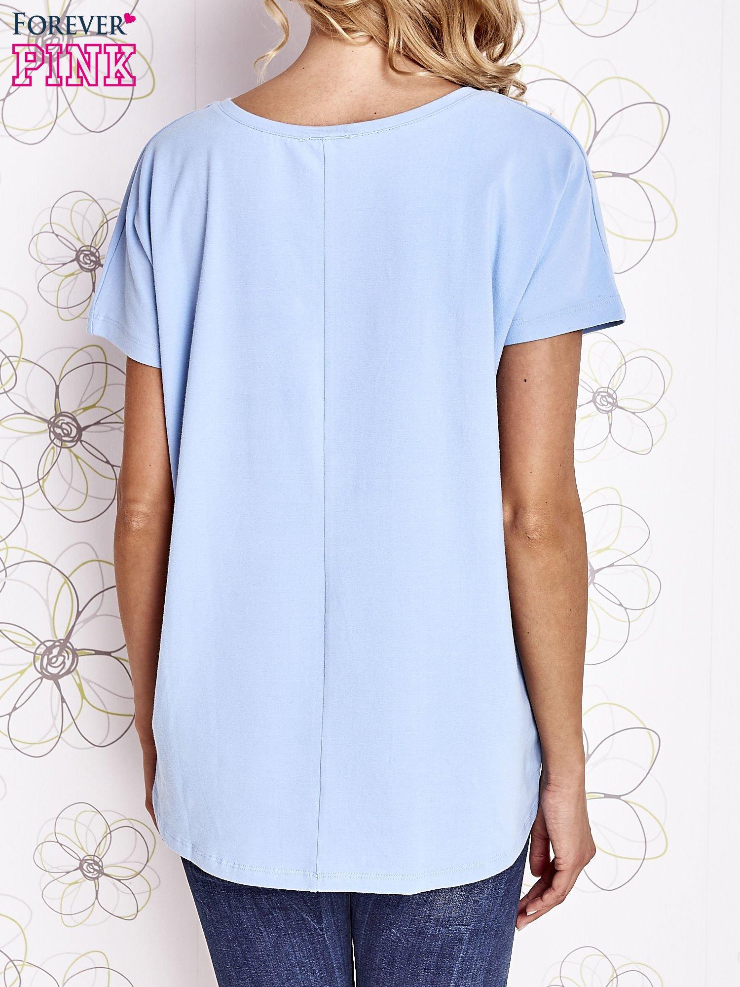 Jasnoniebieski t-shirt z ozdobnym napisem i kokardą                                  zdj.                                  4