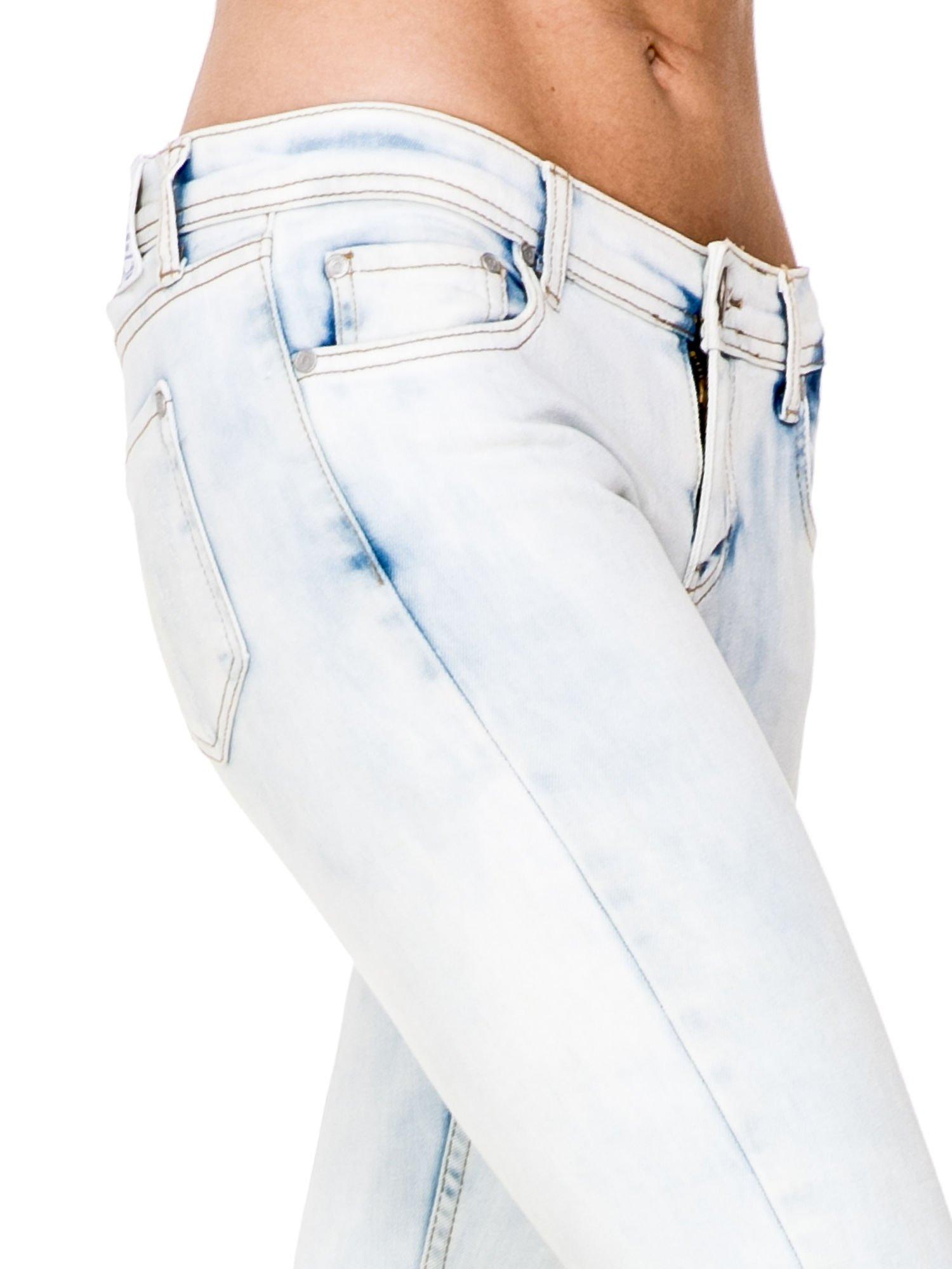 Jasnoniebieskie rozjaśniane spodnie jeaansowe rurki z rozdarciami na kolanach                                  zdj.                                  5