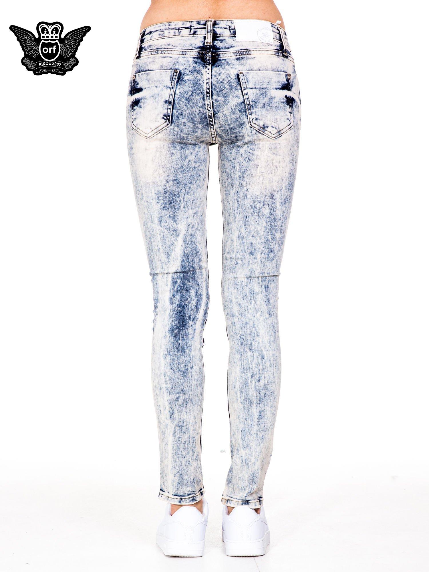 Jasnoniebieskie spodnie jeansowe rurki z dekatyzowaniem i rozdarciami                                  zdj.                                  5