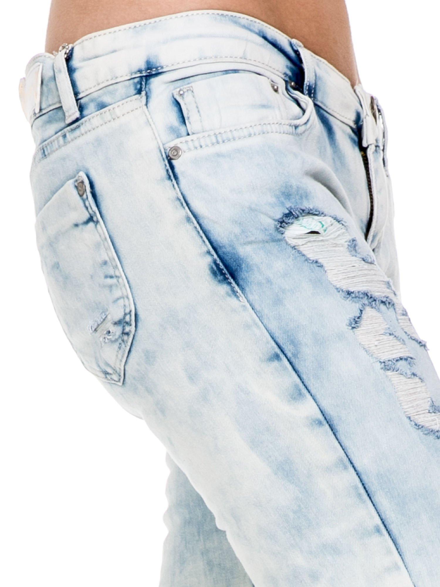 Jasnoniebieskie spodnie jeansowe rurki z przetarciami i poszarpaną na dole nogawką                                  zdj.                                  6