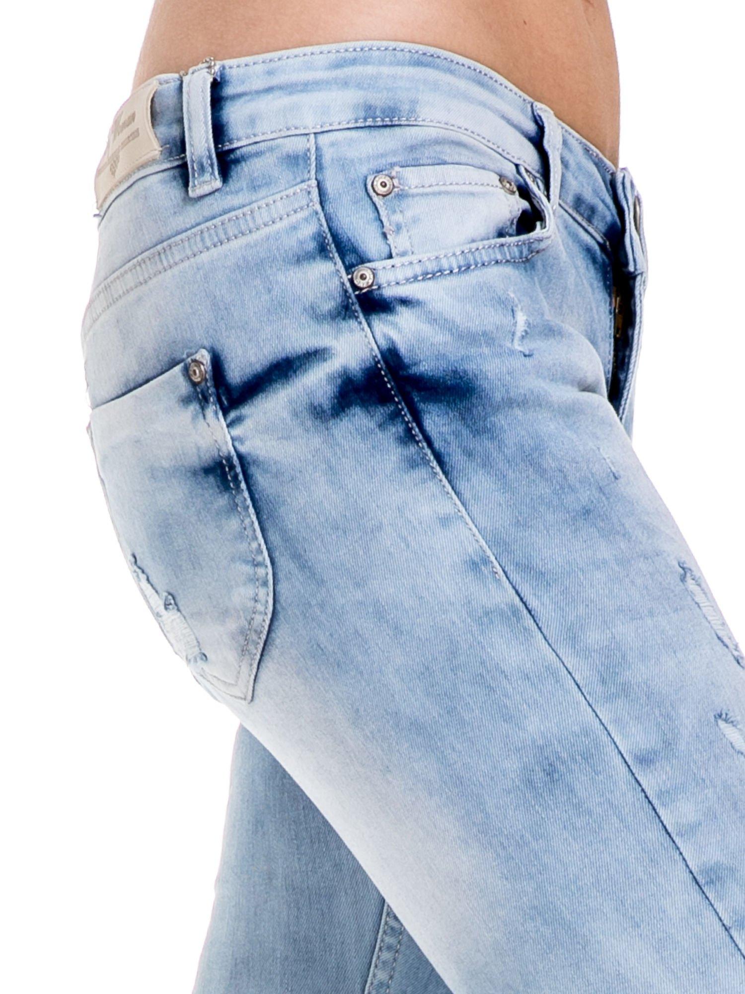 Jasnoniebieskie spodnie jeansowe rurki z rozdarciami i przetarciami                                  zdj.                                  6