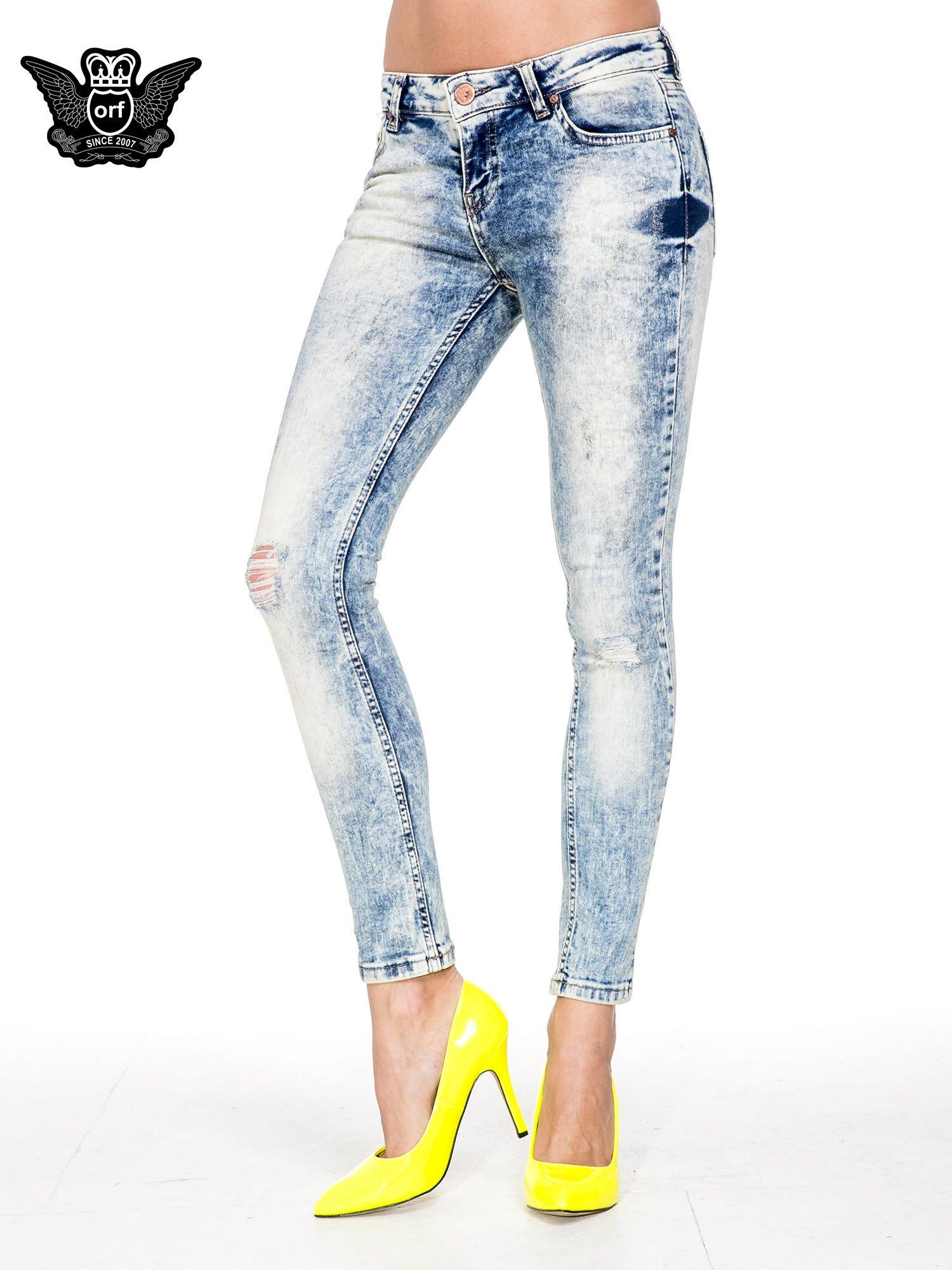 Jasnoniebieskie spodnie skinny jeans z dziurami i modelującym rozjaśnieniem                                  zdj.                                  1