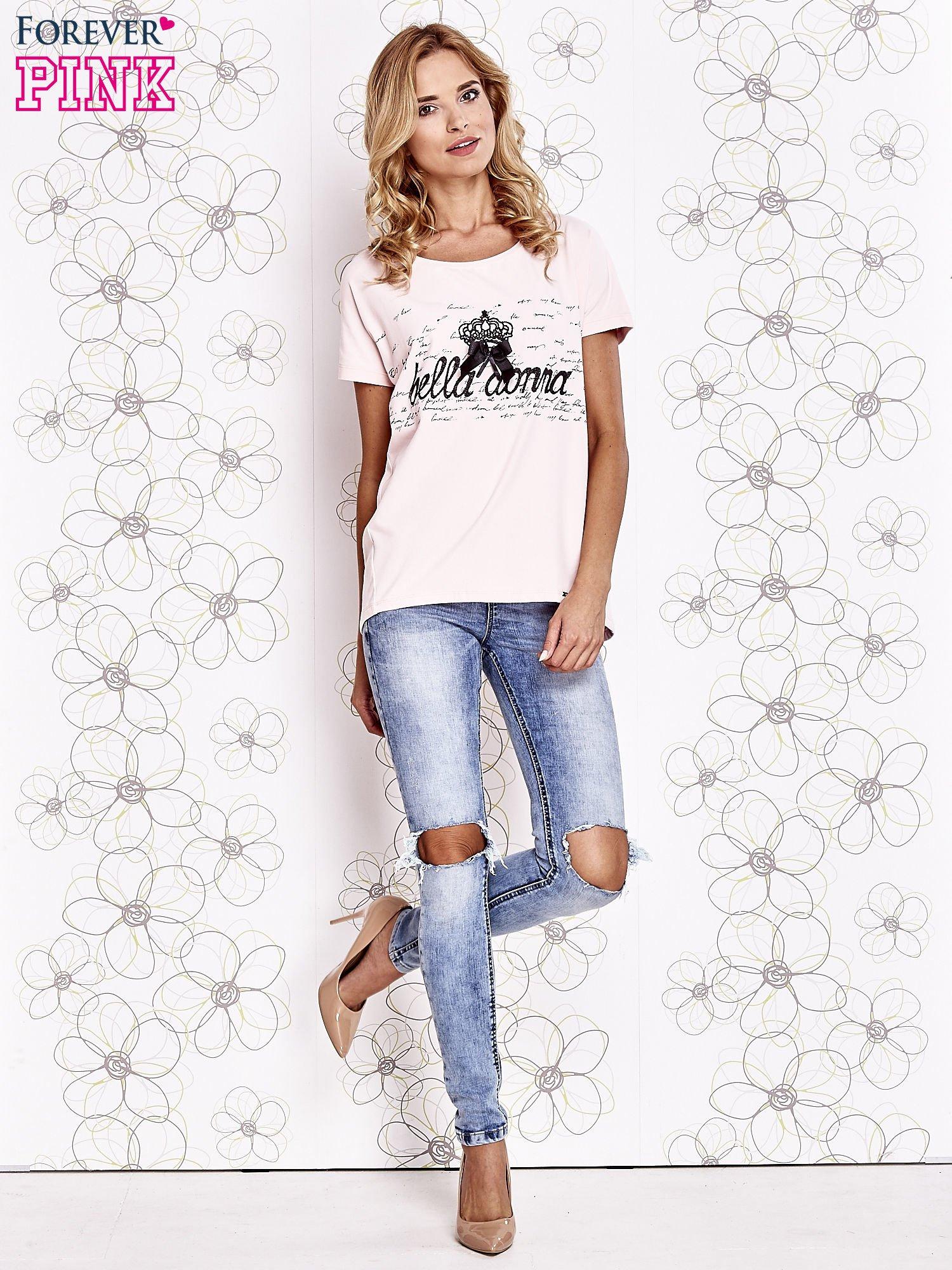 Jasnoróżowy t-shirt z ozdobnym napisem i kokardą                                  zdj.                                  2