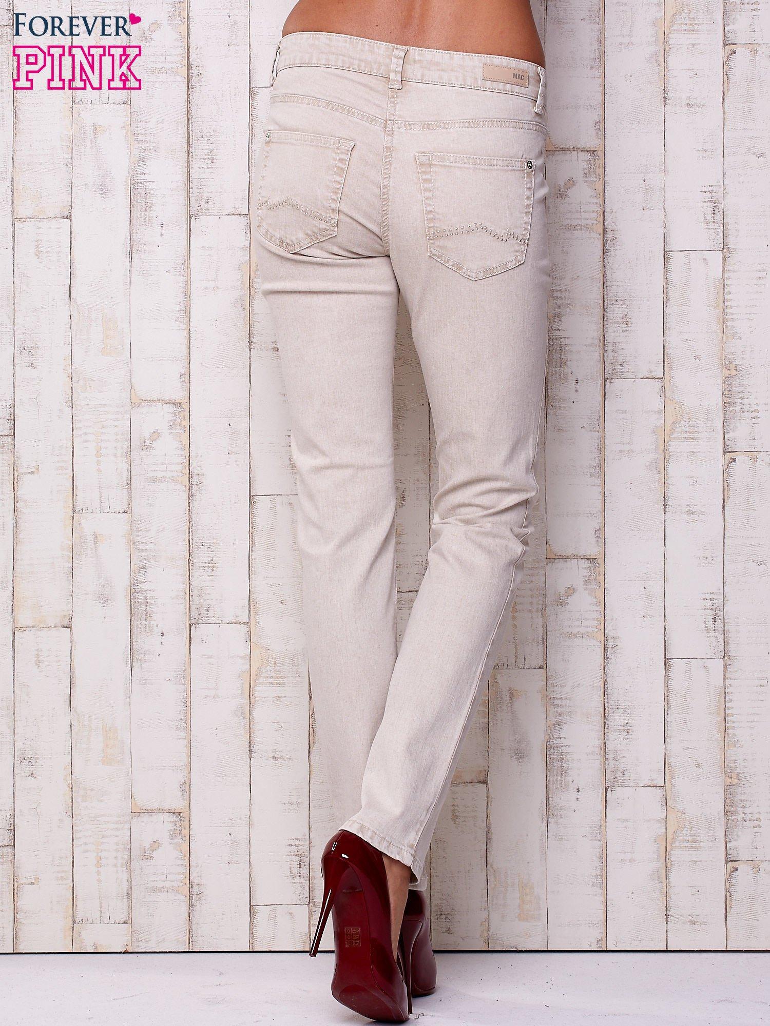 Kremowe proste spodnie ze srebrnymi napami                                  zdj.                                  2