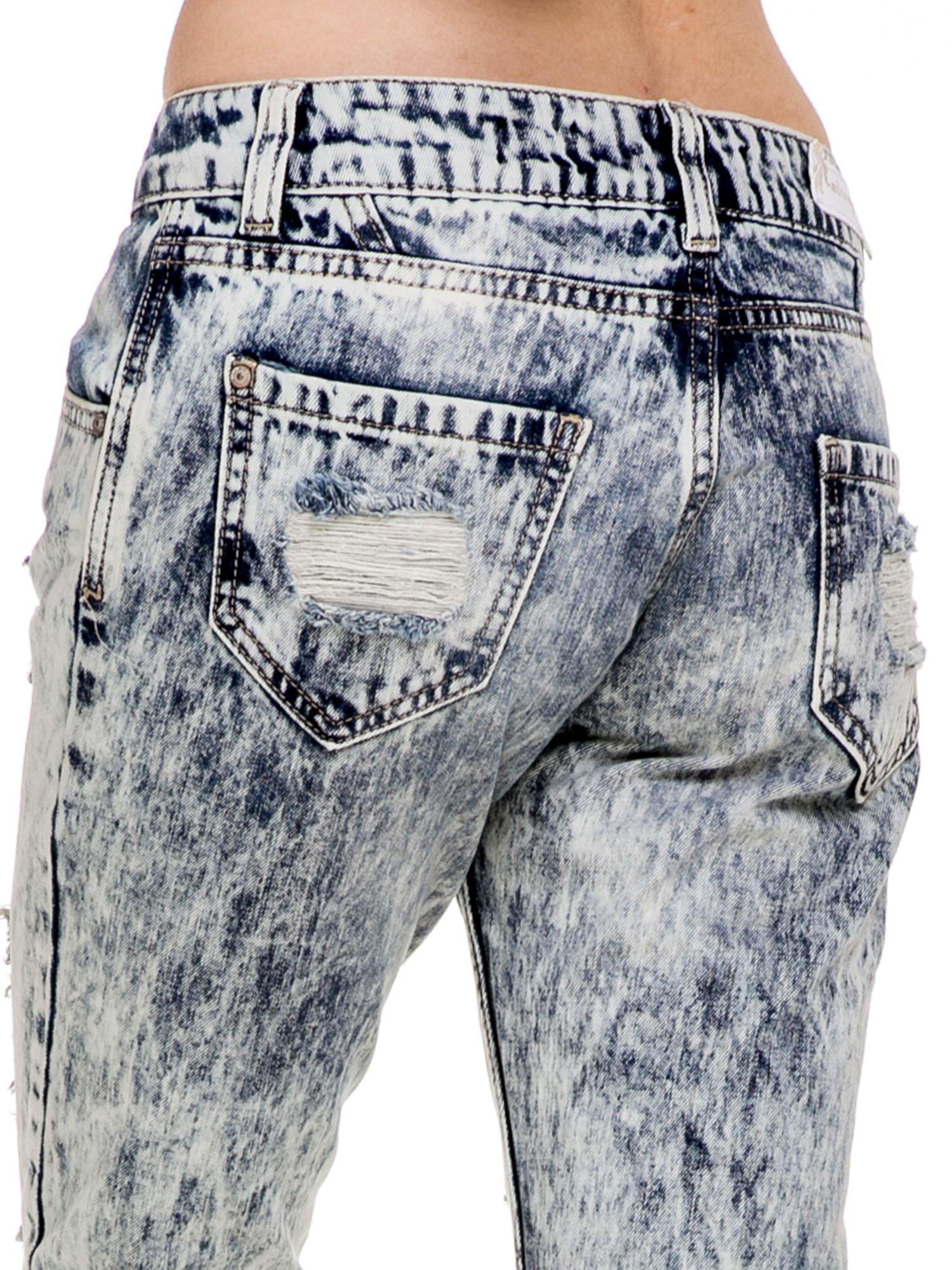 Niebieskie rozjaśniane spodnie jeansowe z przetarciami                                  zdj.                                  4