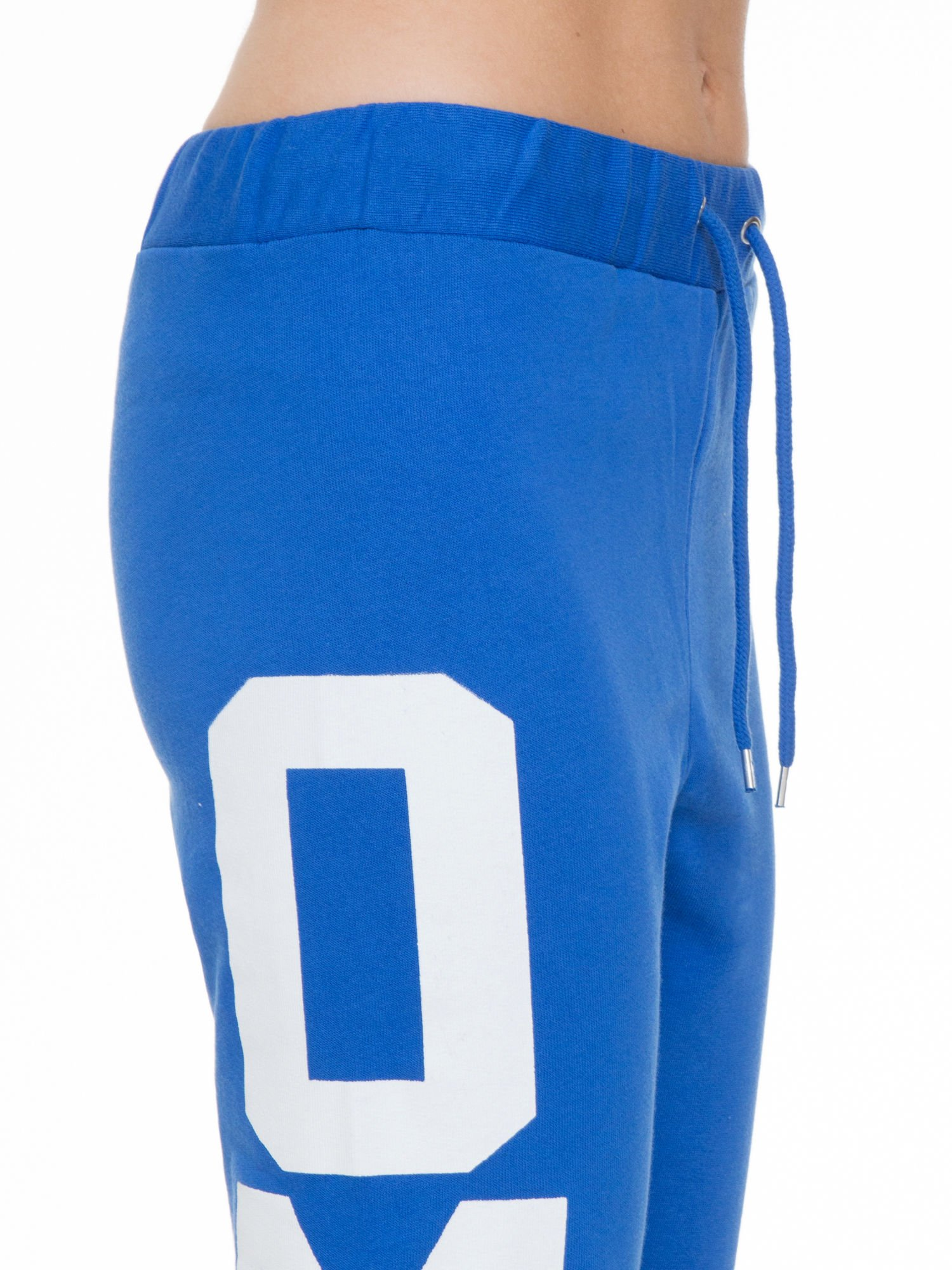 Niebieskie spodnie dresowe z nadrukiem OMG z boku nogawek                                  zdj.                                  5