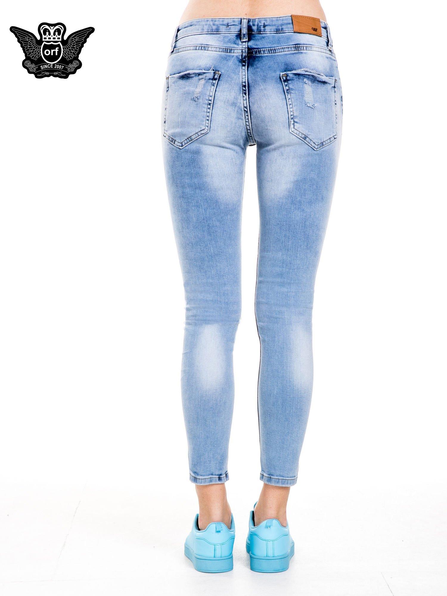 Niebieskie spodnie jeansowe z dziurami i rozdarciami                                  zdj.                                  5