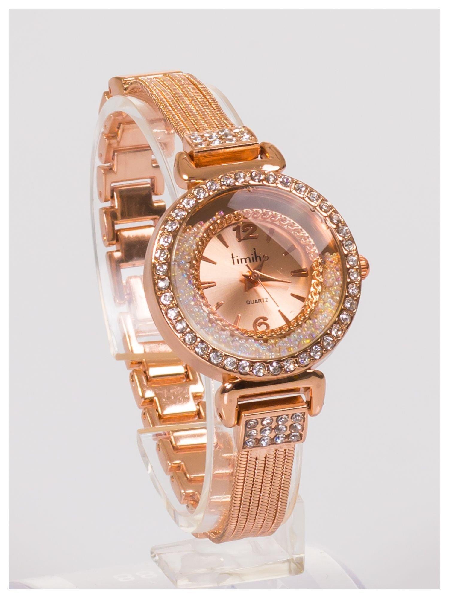 Ozdobny damski zegarek z cyrkoniami, w kolorze różowego złota, na stalowej bransolecie z łańcuszkami                                  zdj.                                  2