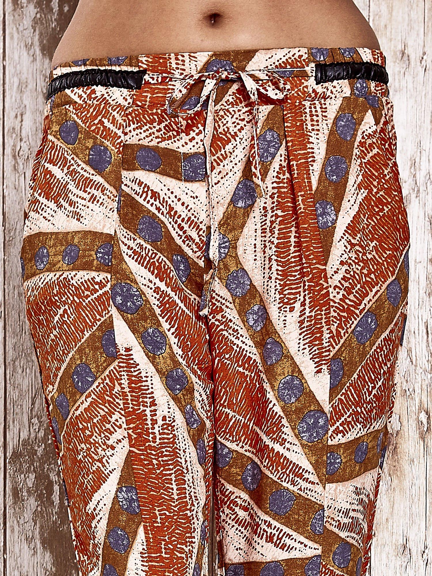 Pomarańczowe lejące spodnie z artystycznym nadrukiem                                  zdj.                                  4