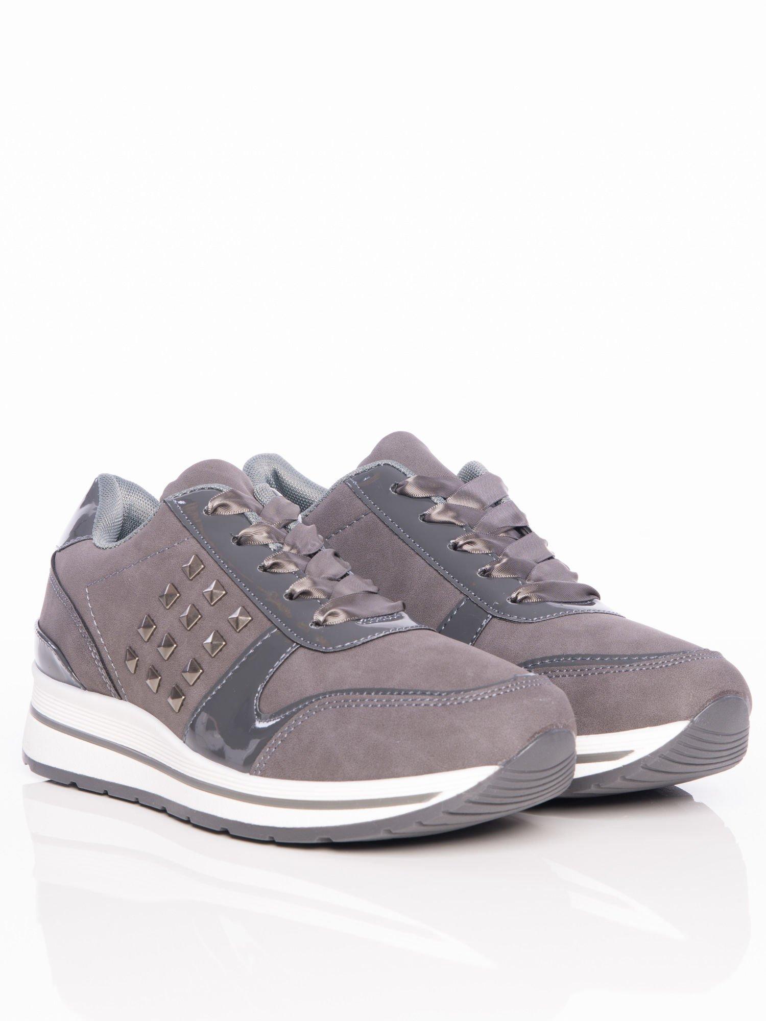 Popielate buty sportowe z lakierowanymi wstawkami i atłasowymi sznurówkami