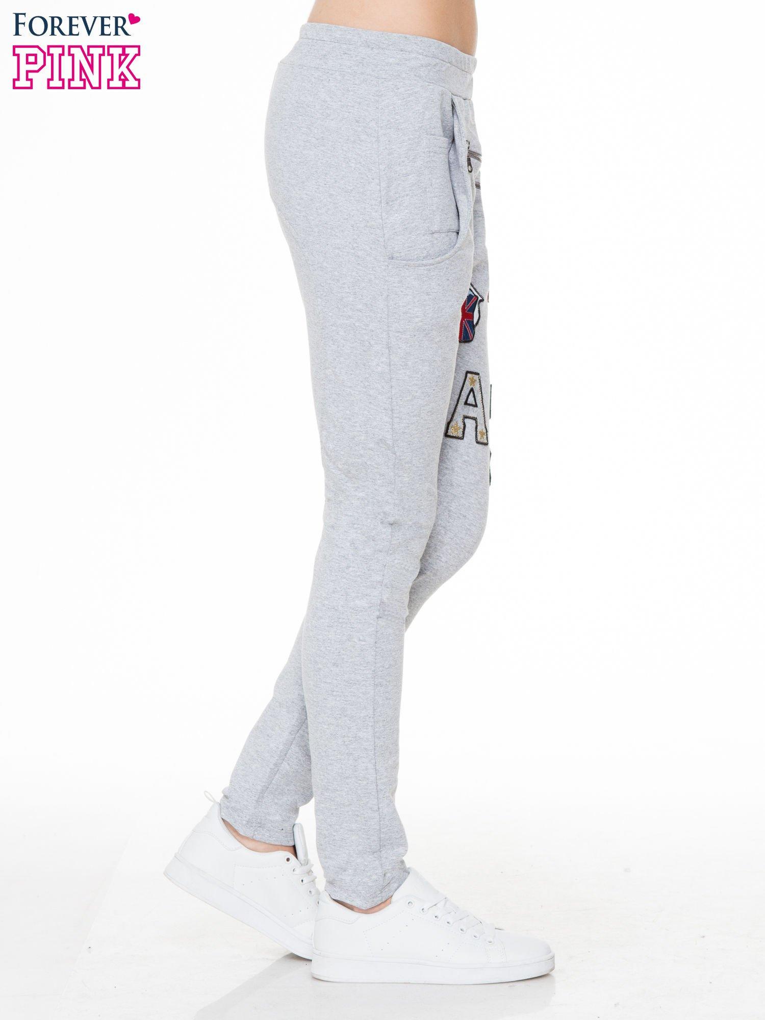 Szare spodnie dresowe typu baggy z naszywkami                                  zdj.                                  3