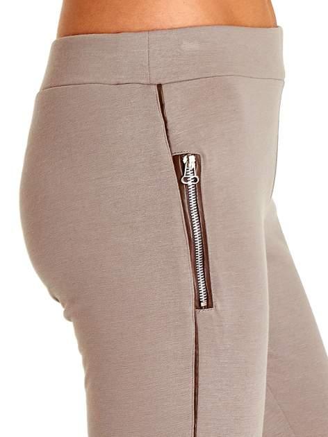 Beżowe spodnie materiałowe tregginsy ze skórzanym lampasem i zamkami                              zdj.                              6