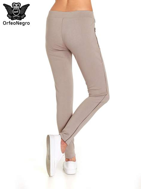 Beżowe spodnie materiałowe tregginsy ze skórzanym lampasem i zamkami                                  zdj.                                  2