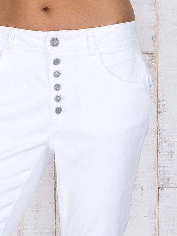 Białe jeansowe spodnie z przetarciami i guzikami                                  zdj.                                  4