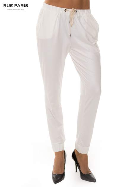 Białe spodnie dresowe ze zwężanymi nogawkami z efektem połysku                                  zdj.                                  1