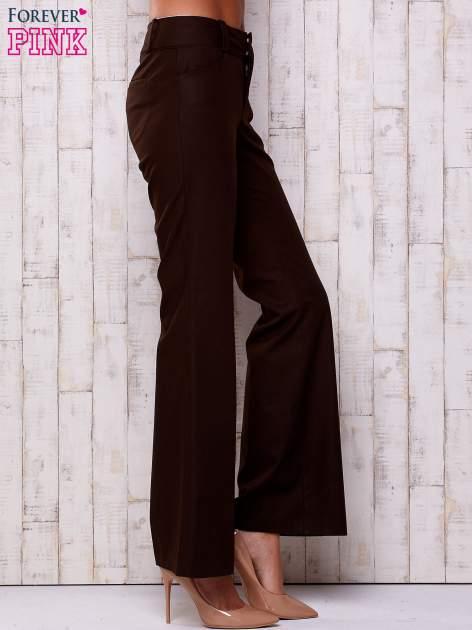 Brązowe materiałowe rozszerzane spodnie                                  zdj.                                  2