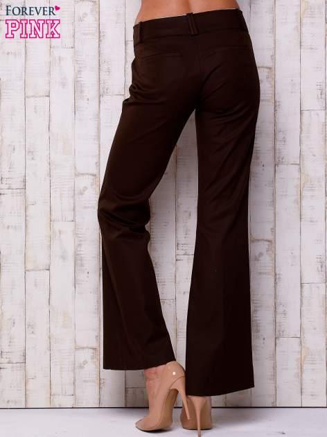 Brązowe materiałowe rozszerzane spodnie                                  zdj.                                  3