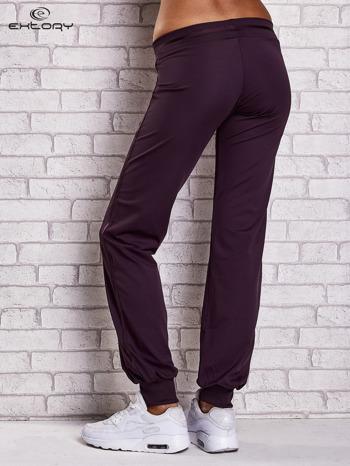 Ciemnofioletowe spodnie dresowe z ozdobnym paskiem                                  zdj.                                  2
