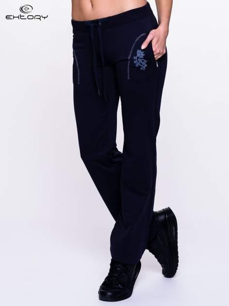 Ciemnogranatowe spodnie dresowe z kwiatem z dżetami i przeszyciem                                  zdj.                                  1