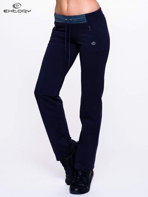 Ciemnogranatowe spodnie dresowe z turkusową wstawką