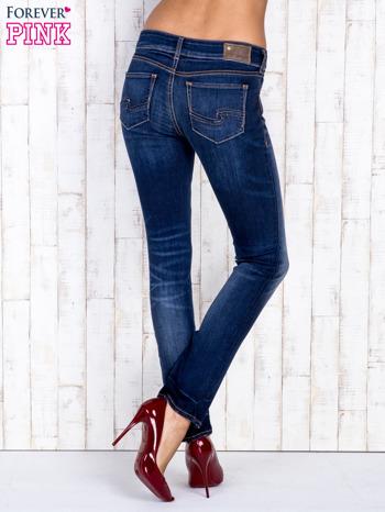 Ciemnoniebieskie jeansowe spodnie slim z przetarciami                                  zdj.                                  3