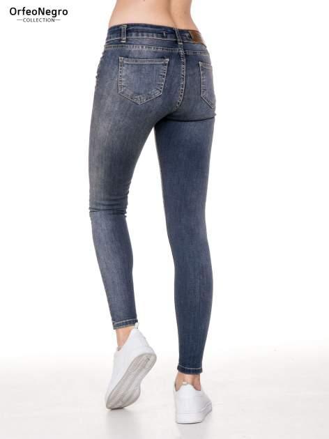 Ciemnoniebieskie rozjaśniane spodnie jeansowe rurki z przetarciami                              zdj.                              4