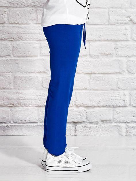 Ciemnoniebieskie spodnie dresowe dla dziewczynki z nadrukiem serc                              zdj.                              3