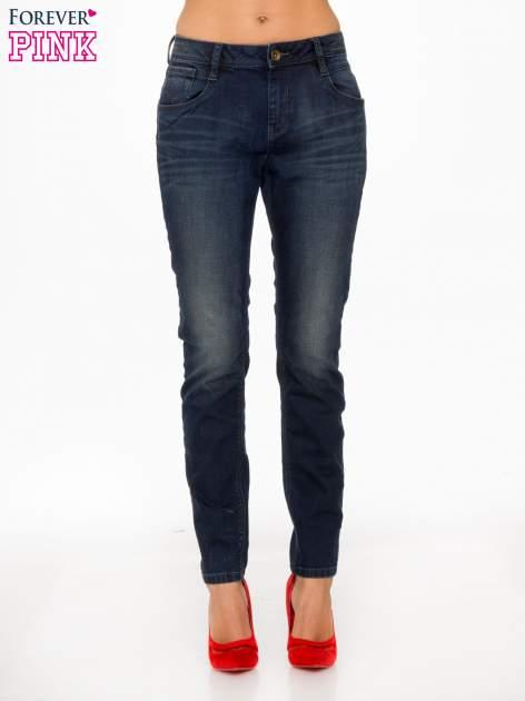 Ciemnoniebieskie spodnie jeansowe rurki z trójkątnymi kieszeniami tylnymi