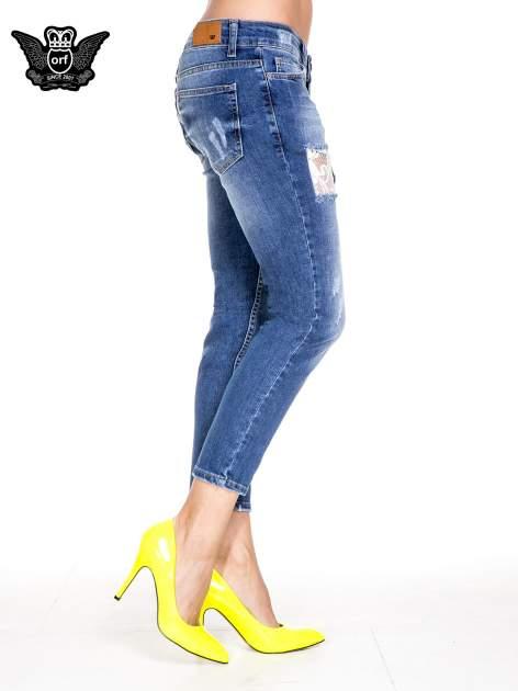 Ciemnoniebieskie spodnie jeansowe z dziurami podszytymi koronką                                  zdj.                                  3