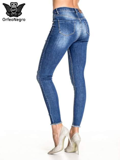 Ciemnoniebieskie spodnie skinny jeans z poszarpaną nogawką i dziurami                                  zdj.                                  4