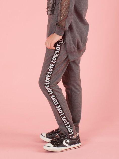 Ciemnoszare spodnie dresowe dziecięce z cekinowym lampasem                              zdj.                              3