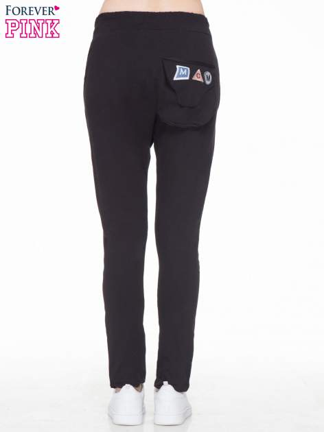 Czarne dresowe spodnie baggy z guzikami i ozdobnymi kieszonkami