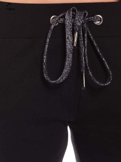 Czarne dresowe spodnie damskie ze ściągaczem i błyszczącym sznurkiem                                  zdj.                                  3