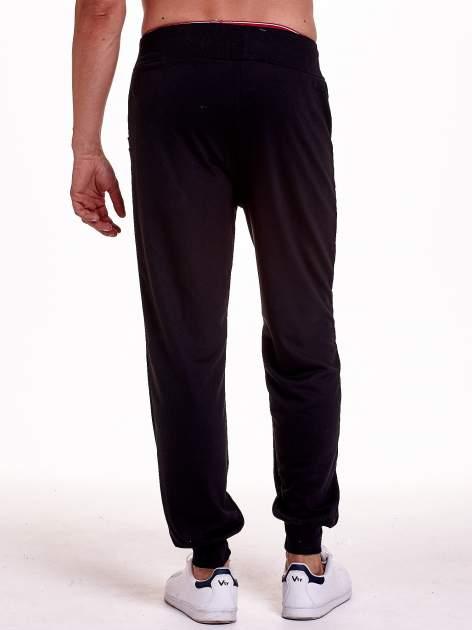 Czarne dresowe spodnie męskie z trokami w pasie i kieszeniami                                  zdj.                                  4