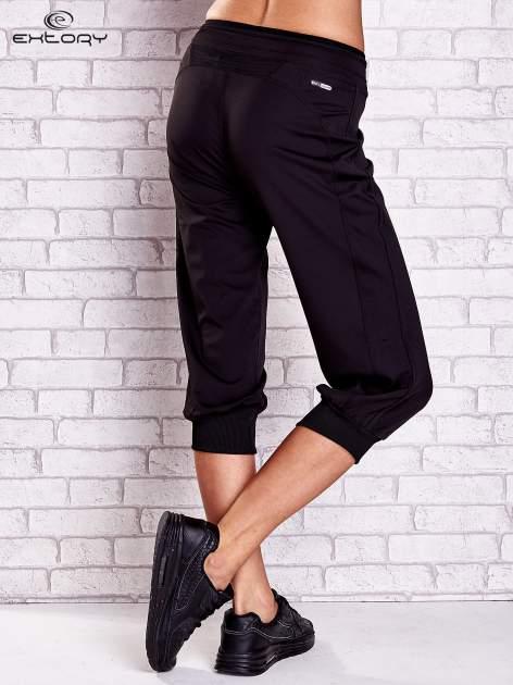Czarne spodnie capri z lampasami i troczkami PLUS SIZE                                  zdj.                                  2