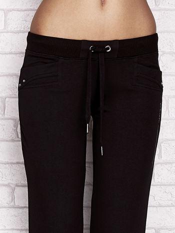 Czarne spodnie dresowe capri z dżetami na kieszeniach                                  zdj.                                  4
