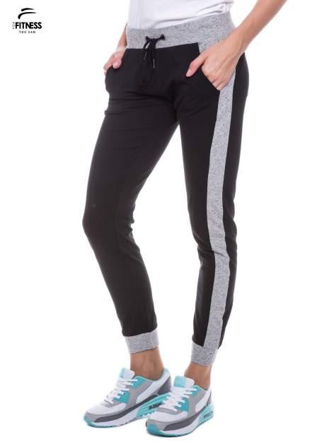 Czarne spodnie dresowe damskie z kontrastowymi lampasami po bokach                                  zdj.                                  3