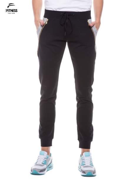 Czarne spodnie dresowe damskie z suwakiem i kontrastowymi wstawkami po bokach