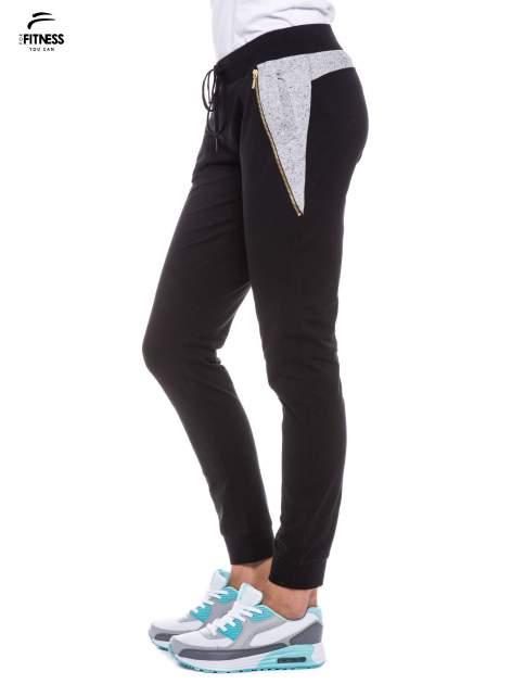 Czarne spodnie dresowe damskie z suwakiem i kontrastowymi wstawkami po bokach                                  zdj.                                  2
